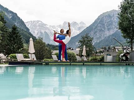 Couple doing yoga by the pool
